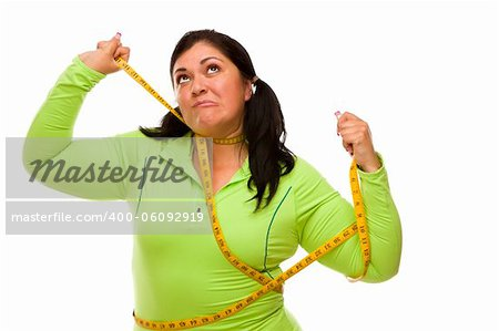 Attractive Frustrated Hispanic Woman Tied Up With Tape Measure Against a White Background. Stock Photo - Budget Royalty-Free, Image code: 400-06092919