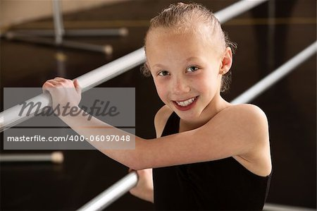 Smiling ballerina girl holding balance bars in dance studio Stock Photo - Budget Royalty-Free, Image code: 400-06097048