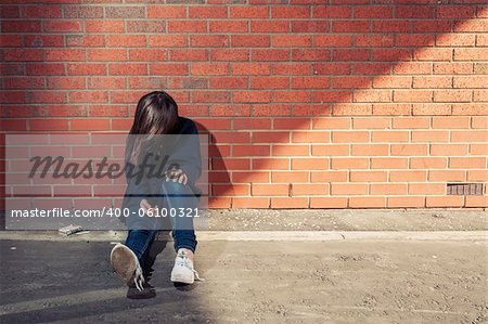 Addicted, sad young woman sitting against the brick wall with syringe and cigarettes beside.  Horizontal. Stock Photo - Budget Royalty-Free, Image code: 400-06100321