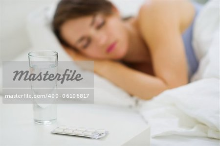 Closeup on pills and glass of water on table and sleeping woman in background Stock Photo - Budget Royalty-Free, Image code: 400-06106817