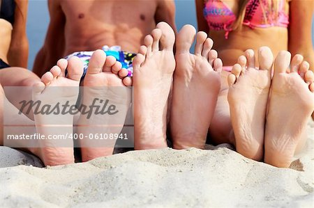 Soles of teenagers sunbathing on sandy beach Stock Photo - Budget Royalty-Free, Image code: 400-06108941