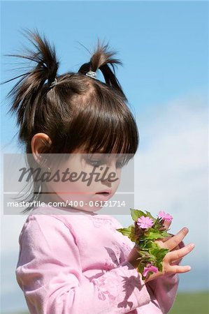 Little girl with pigtails holding a handful of pink wild flowers. Stock Photo - Budget Royalty-Free, Image code: 400-06131714