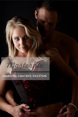 Young and fit caucasian adult couple in an embrace. Semi-nude and topless against a dark background with the woman wearing a sexy red and black lace corset.. Stock Photo - Budget Royalty-Free, Image code: 400-06137146