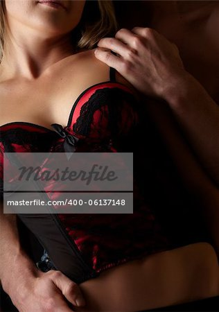 Young and fit caucasian adult couple in an embrace. Semi-nude and topless against a dark background with the woman wearing a sexy red and black lace corset.. Stock Photo - Budget Royalty-Free, Image code: 400-06137148