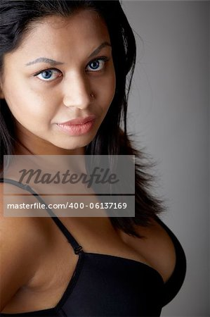 Young voluptuous Indian adult woman with long black hair wearing black lingerie and blue coloured contact lenses on a neutral grey background. Mixed ethnicity Stock Photo - Budget Royalty-Free, Image code: 400-06137169