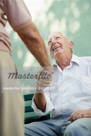 Active retirement, two old male friends talking and shaking hands on bench in public park Stock Photo - Budget Royalty-Free, Image code: 400-06142277
