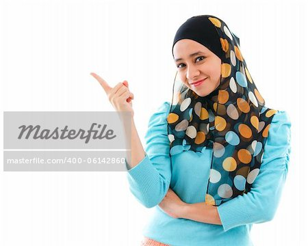 Cute young Muslim woman pointing on empty space, isolated on white Stock Photo - Budget Royalty-Free, Image code: 400-06142860