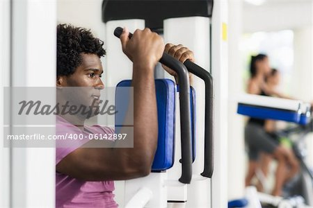 Young black man exercising pectoral muscles in fitness club, with people working out on cyclette in background Stock Photo - Budget Royalty-Free, Image code: 400-06142897