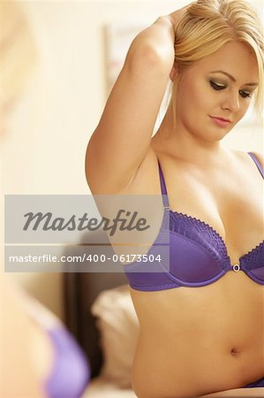 Young adult caucasian woman in purple lingerie looking at herself in a wall mirror while holding her blonde hair up with one hand. Stock Photo - Budget Royalty-Free, Image code: 400-06173504