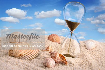 Hourglass in the sand with blue sky Stock Photo - Budget Royalty-Free, Image code: 400-06203345