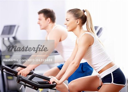 Young people on bikes in a fitness club Stock Photo - Budget Royalty-Free, Image code: 400-06355488