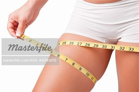 Woman measuring her thigh with a yellow measuring tape Stock Photo - Budget Royalty-Free, Image code: 400-06391672