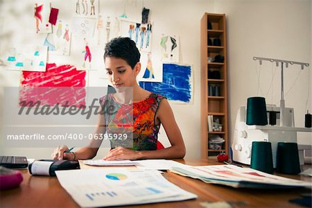 Money and financial planning, young hispanic self-employed woman checking bills and doing budget with calculator, computer and papers in fashion design studio Stock Photo - Budget Royalty-Free, Image code: 400-06395929
