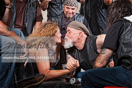 Two biker gang lovers kiss while arm wrestling Stock Photo - Budget Royalty-Free, Image code: 400-06396543