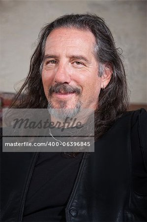 Smiling long haired male with leather vest Stock Photo - Budget Royalty-Free, Image code: 400-06396845