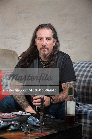 Serious biker gang member with liquor and dagger on table Stock Photo - Budget Royalty-Free, Image code: 400-06396846