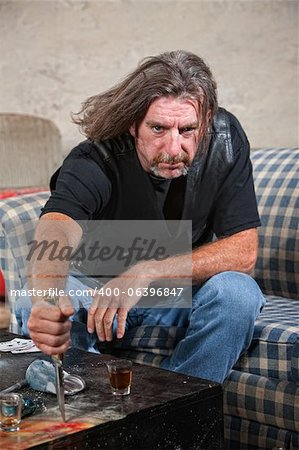 Angry Caucasian male gang member with knife and shot glass on table Stock Photo - Budget Royalty-Free, Image code: 400-06396847