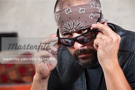 Intimidating male biker in bandana looking over his sunglasses Stock Photo - Budget Royalty-Free, Image code: 400-06396855