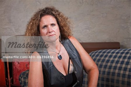 Serious mature biker woman in leather vest sitting indoors Stock Photo - Budget Royalty-Free, Image code: 400-06396856