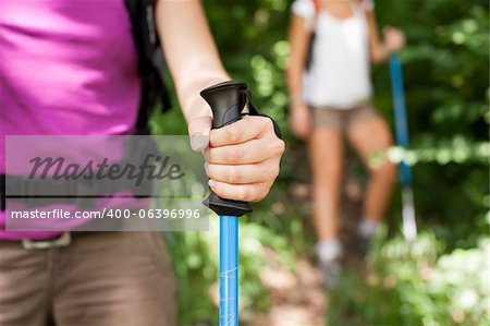 young female friends walking in woods. Closeup of hand holding stick Stock Photo - Budget Royalty-Free, Image code: 400-06396996