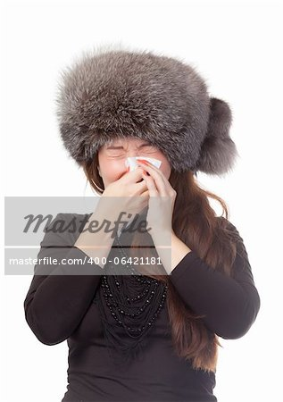 Woman with a winter cold and flu wearing a warm fur hat and blowing her nose on a tissue isolated on white Stock Photo - Budget Royalty-Free, Image code: 400-06421181