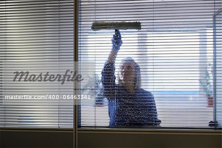 Woman at work, professional female cleaner cleaning and wiping window in office with detergent Stock Photo - Budget Royalty-Free, Image code: 400-06463341