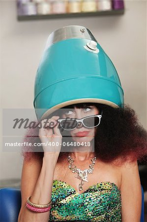 Pouting lady with frizzy hair sitting under hair dryer Stock Photo - Budget Royalty-Free, Image code: 400-06480418