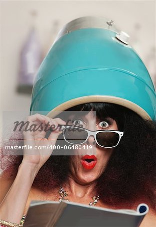 Surprised female reading magazine while under hair dryer Stock Photo - Budget Royalty-Free, Image code: 400-06480419