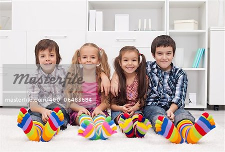 Happy children sitting on the carpet wearing colorful socks Stock Photo - Budget Royalty-Free, Image code: 400-06483684