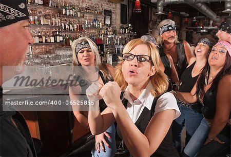 Female geek puts up fist to tough man in bar Stock Photo - Budget Royalty-Free, Image code: 400-06525855
