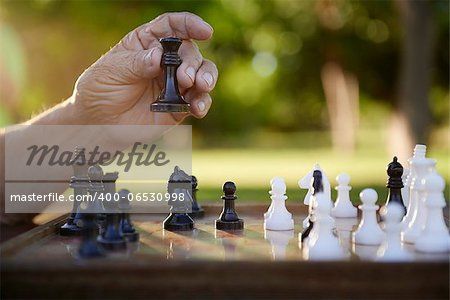 Active retired persons, hand of old man holding chess piece in park. Closeup shot, copy space Stock Photo - Budget Royalty-Free, Image code: 400-06530998