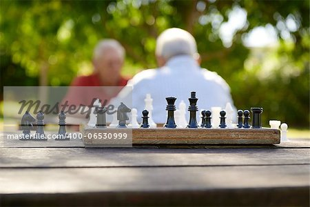 Active retirement, old friends and leisure, two senior men having fun and playing chess game at park. Focus on chessboard in foreground Stock Photo - Budget Royalty-Free, Image code: 400-06530999