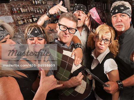 Nerd husband and wife being cool with biker gang in bar Stock Photo - Budget Royalty-Free, Image code: 400-06558609
