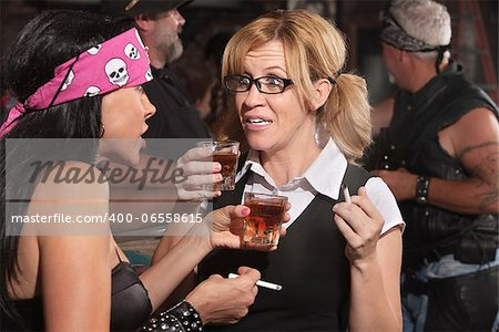 Blond woman and biker gang lady talking while smoking and drinking Stock Photo - Budget Royalty-Free, Image code: 400-06558615