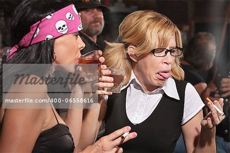 Female nerd sticking out tongue after tasting whiskey in bar Stock Photo - Budget Royalty-Free, Image code: 400-06558616