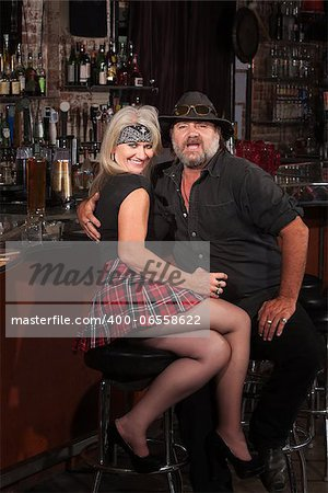 Happy middle aged motorcycle gang couple sitting at bar counter Stock Photo - Budget Royalty-Free, Image code: 400-06558622