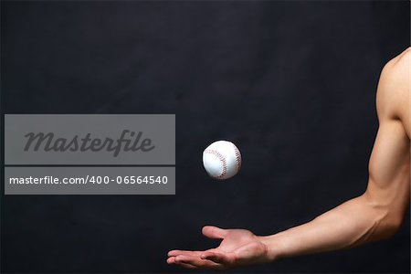Image of male arm playing with baseball ball over black background Stock Photo - Budget Royalty-Free, Image code: 400-06564540
