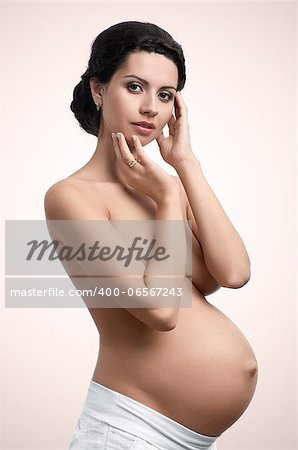 Beautiful figure of young pregnant woman looking in camera Stock Photo - Budget Royalty-Free, Image code: 400-06567243