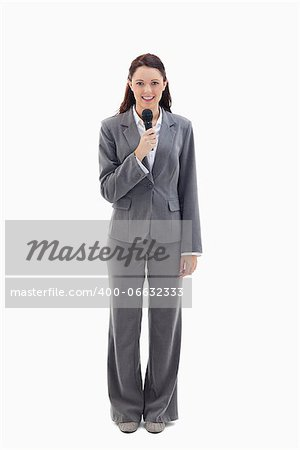 Businesswoman smiling and holding a microphone against white background Stock Photo - Budget Royalty-Free, Image code: 400-06632333