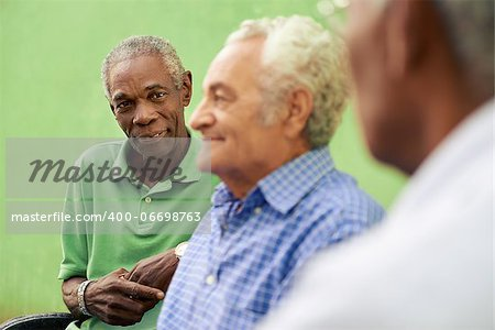 retired elderly people and free time, group of happy senior african american and caucasian male friends talking and sitting on bench in park Stock Photo - Budget Royalty-Free, Image code: 400-06698763