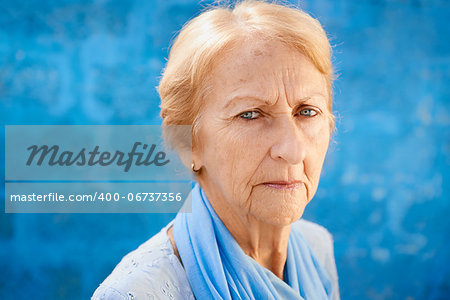 Senior people portrait, happy sad blonde woman in blu clothes looking at camera against blue wall Stock Photo - Budget Royalty-Free, Image code: 400-06737356
