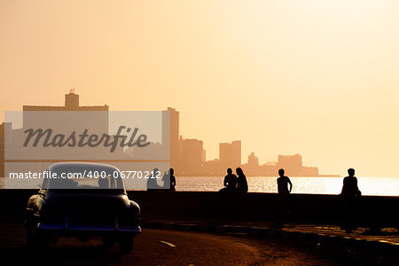 Skyline in La Habana, Cuba, at sunset, with vintage cars on the street and people sitting on the Malecon. Copy space Stock Photo - Budget Royalty-Free, Image code: 400-06770212