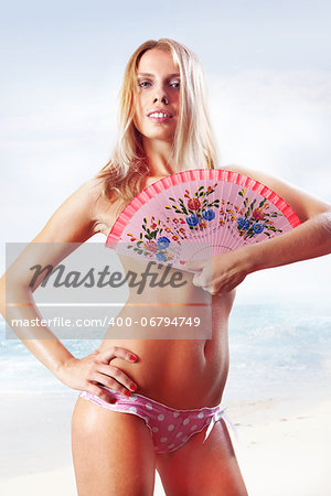 beautiful tanned woman in pink bikini holding fan on beach Stock Photo - Budget Royalty-Free, Image code: 400-06794749