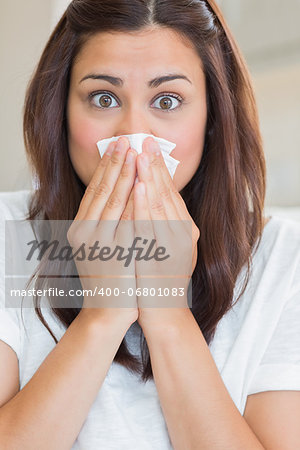 Brunette with runny nose at home looking surprised Stock Photo - Budget Royalty-Free, Image code: 400-06801083