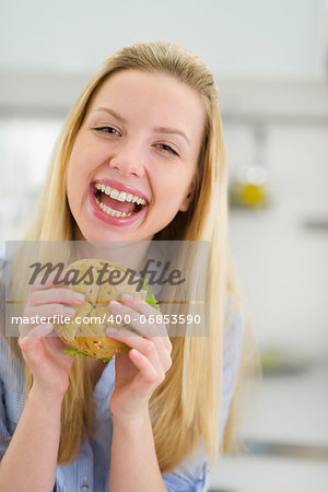 Smiling teenager girl eating sandwich in kitchen Stock Photo - Budget Royalty-Free, Image code: 400-06853590