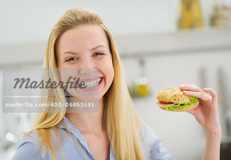 Happy teenager girl eating sandwich in kitchen Stock Photo - Budget Royalty-Free, Image code: 400-06853591