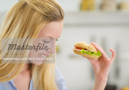 Happy young woman eating sandwich in kitchen Stock Photo - Budget Royalty-Free, Image code: 400-06853592