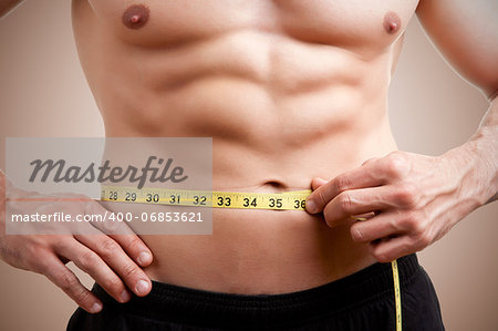 Fit man measuring his waist after a workout in the gym Stock Photo - Budget Royalty-Free, Image code: 400-06853621