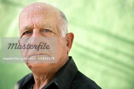 Elderly people and emotions, portrait of serious senior caucasian man looking at camera against green wall Stock Photo - Budget Royalty-Free, Image code: 400-06856678