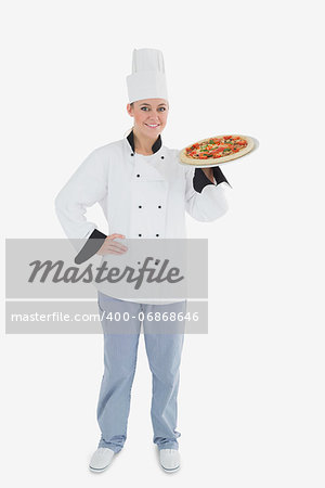 Full length of confident female chef holding pizza over white background Stock Photo - Budget Royalty-Free, Image code: 400-06868646